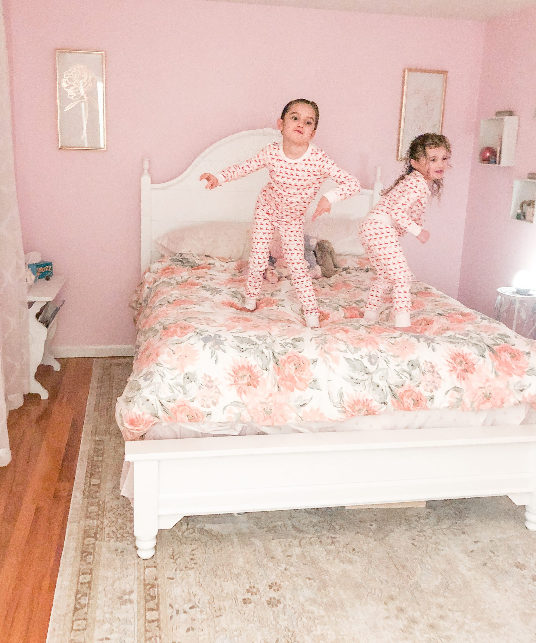 little girls jumping on bed in pink bedroom walls, white bed with floral bedding, white sheer curtains