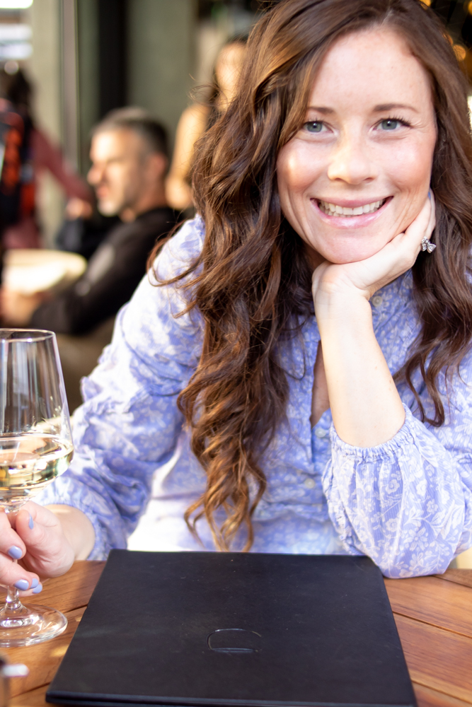 smiling woman wearing periwinkle flower shirt holding a glass of wine