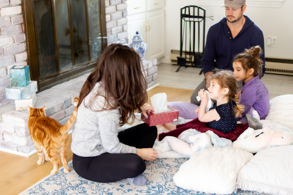 Mom handing tissue box to little girl with dad and sister in background and orange cat