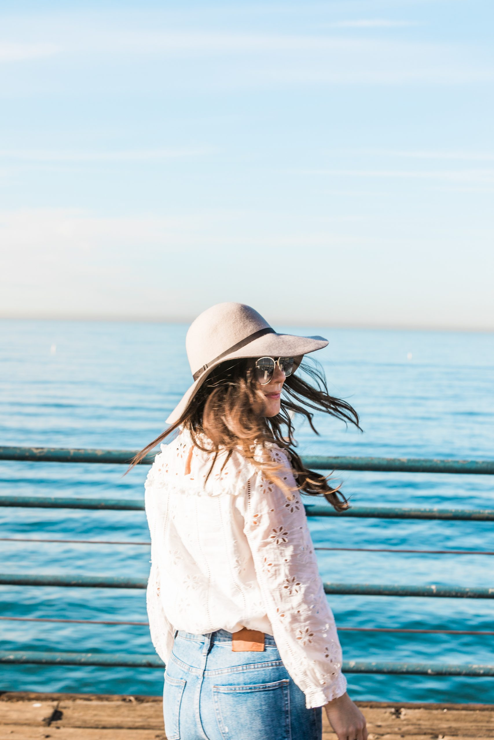 Woman wearing a hat and maxi skirt standing on Santa Monica Beach Pier smiling with ocean in background