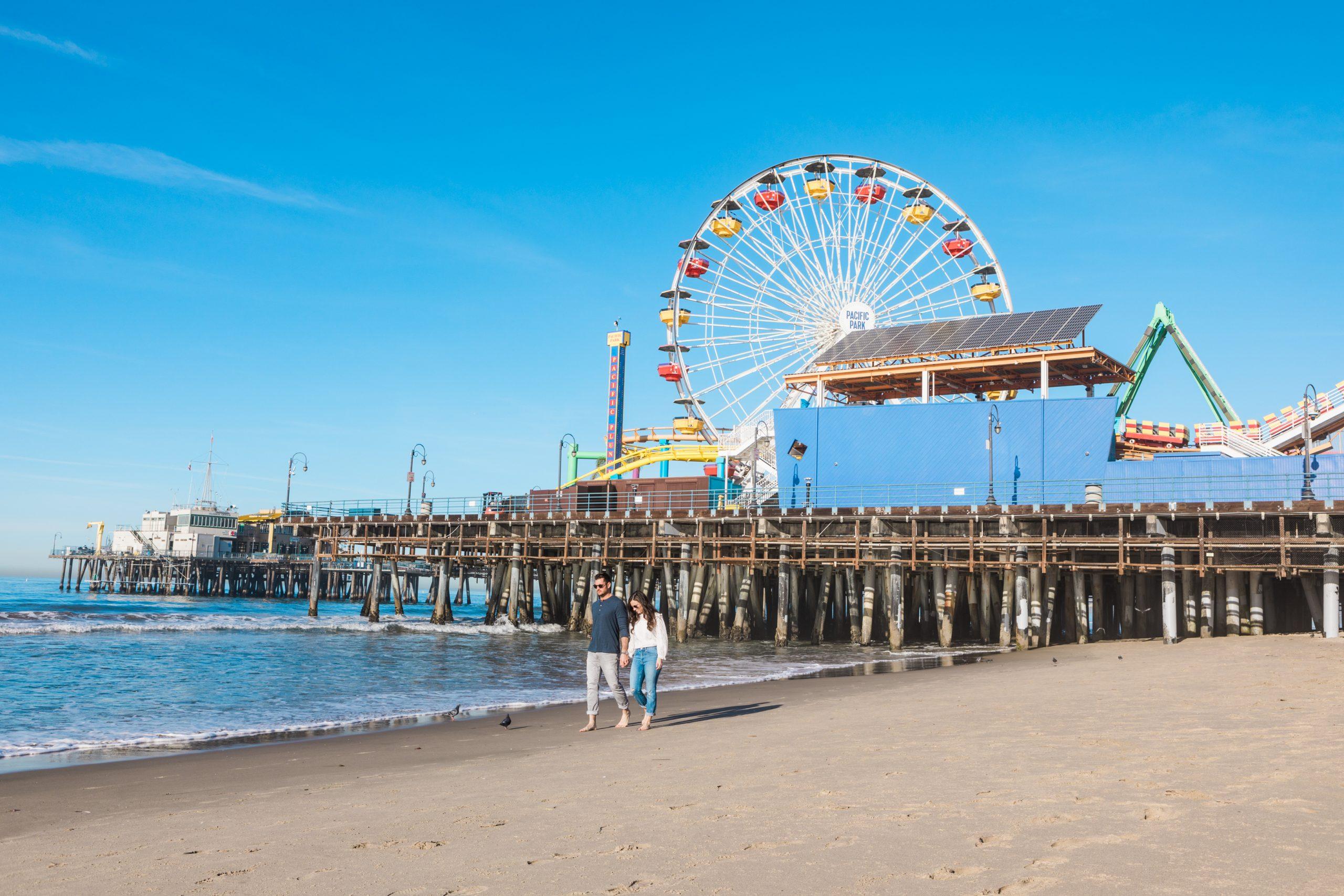 Man and Woman walking on the beach with Santa Monica Beach Pier behind them