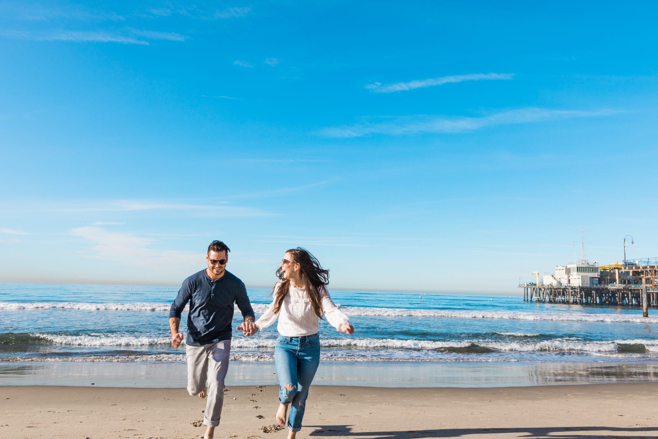 Man and Woman running on Santa Monica Beach away from the ocean