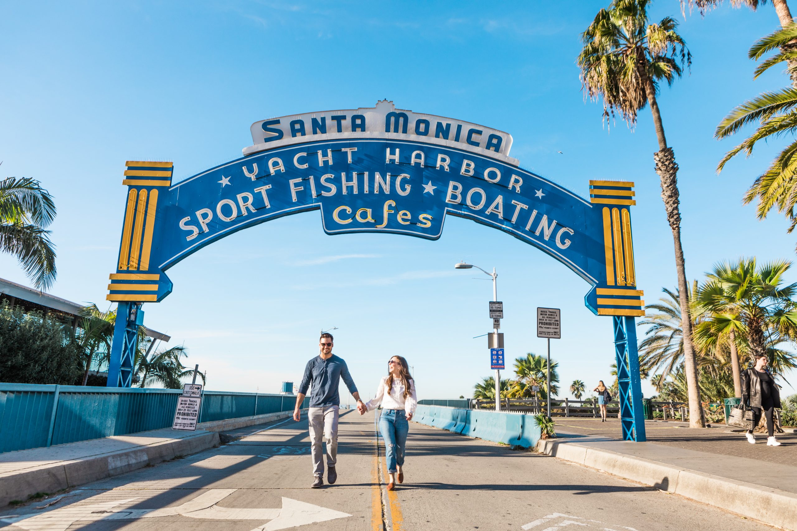 couple holding hands walking under the Santa Monica Yacht Harbor Sign