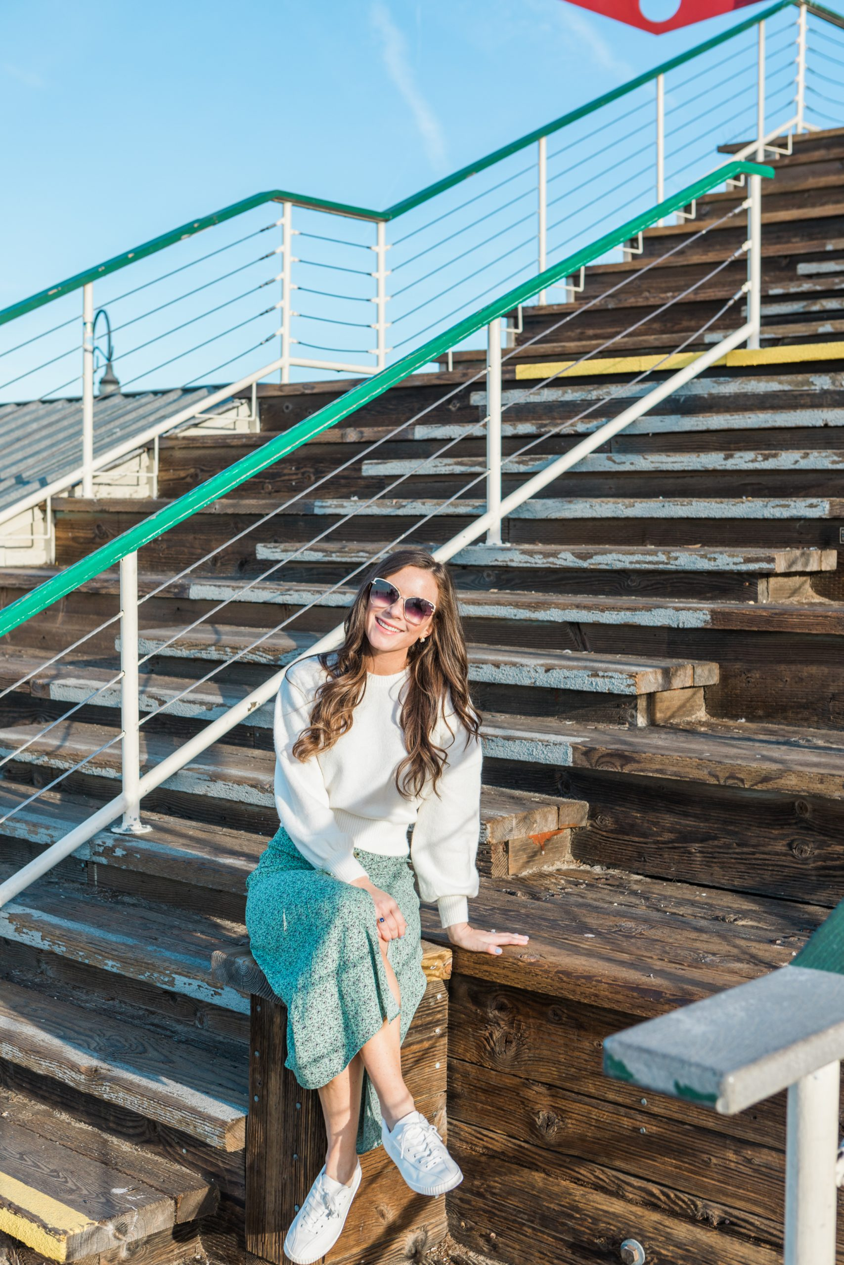 woman sitting on stairs in santa monica wearing a white shirt and green skirt with tretorn sneakers