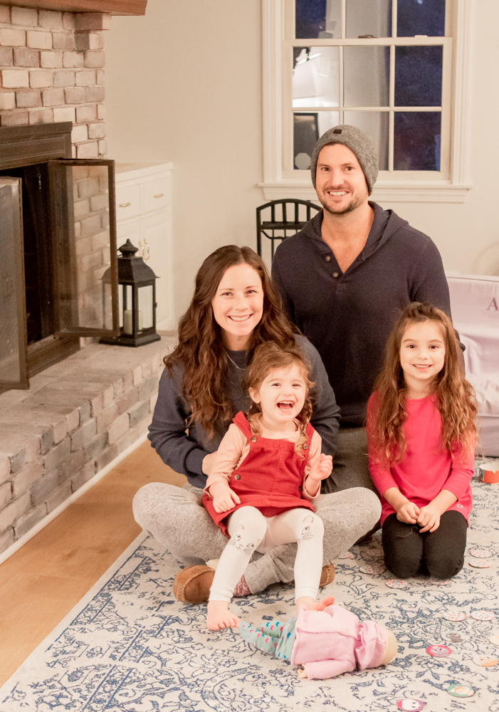 family sitting on rug smiling in front of fireplace