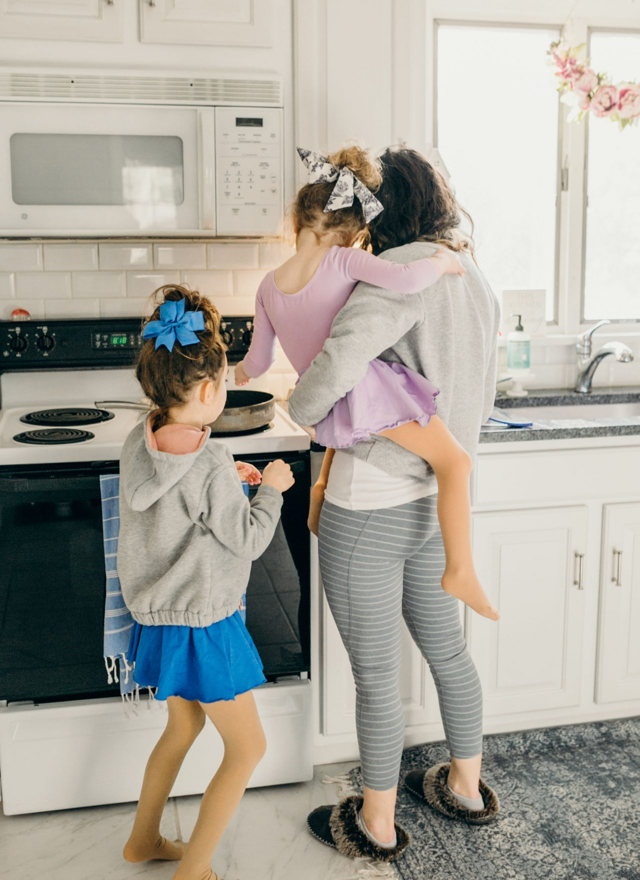 Mom holding daughter cooking in kitchen