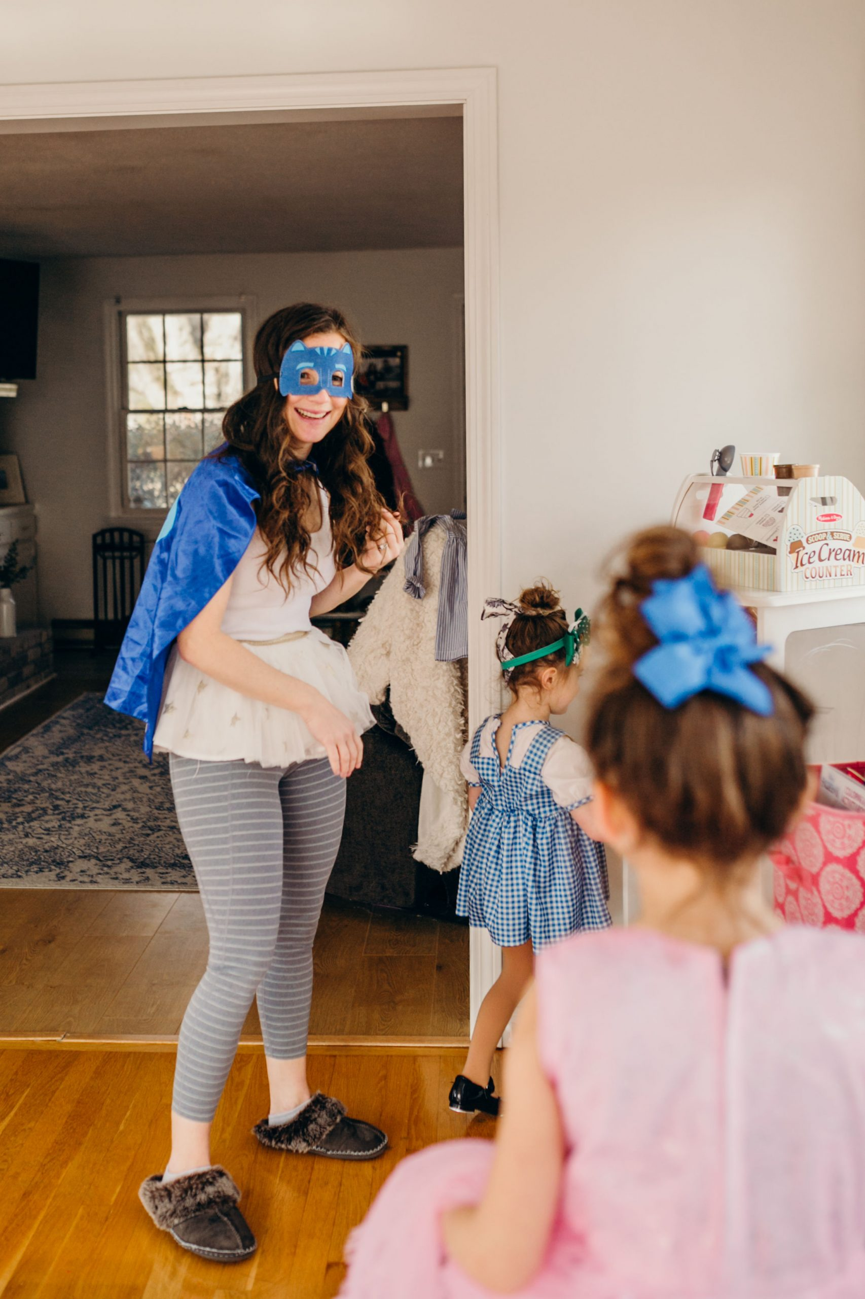 Mom wearing super hero mask and super hero cape with little girls