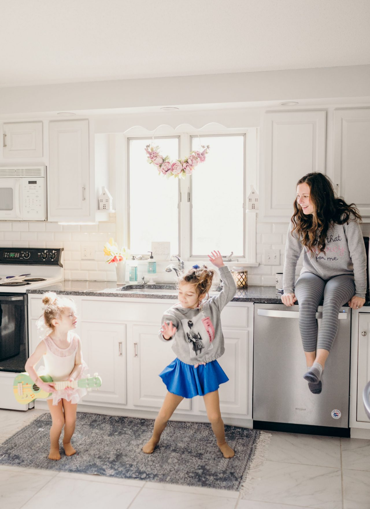 Mom sitting on counter watching kids dance in kitchen