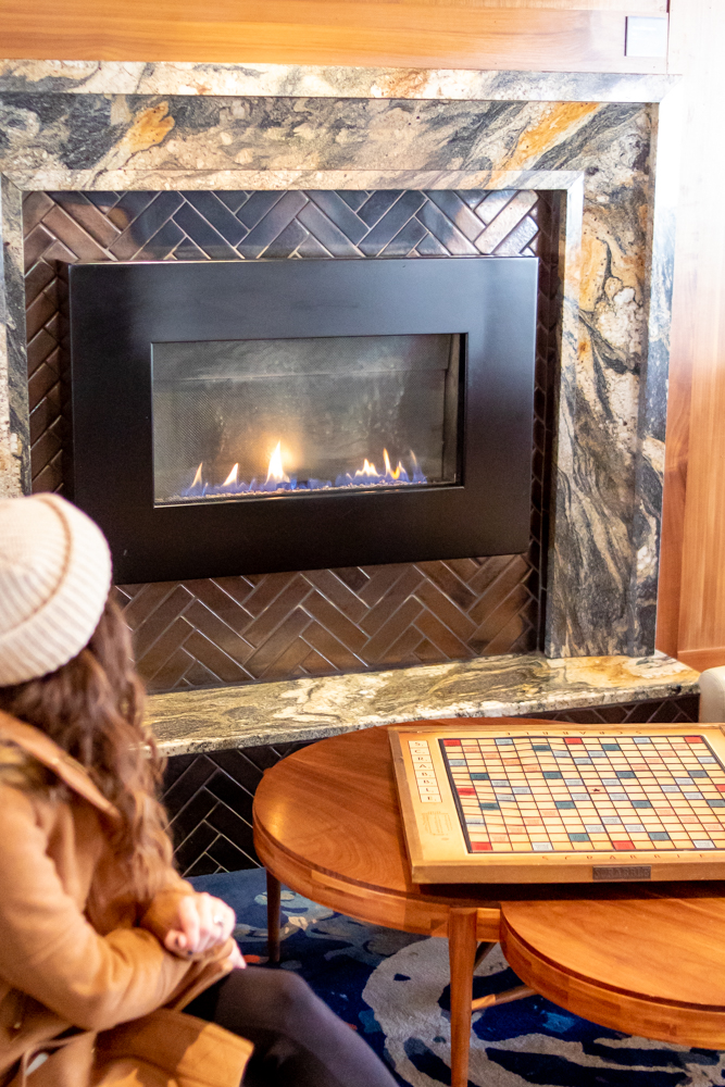 Woman sitting in the Press Hotel Lobby by the fireplace