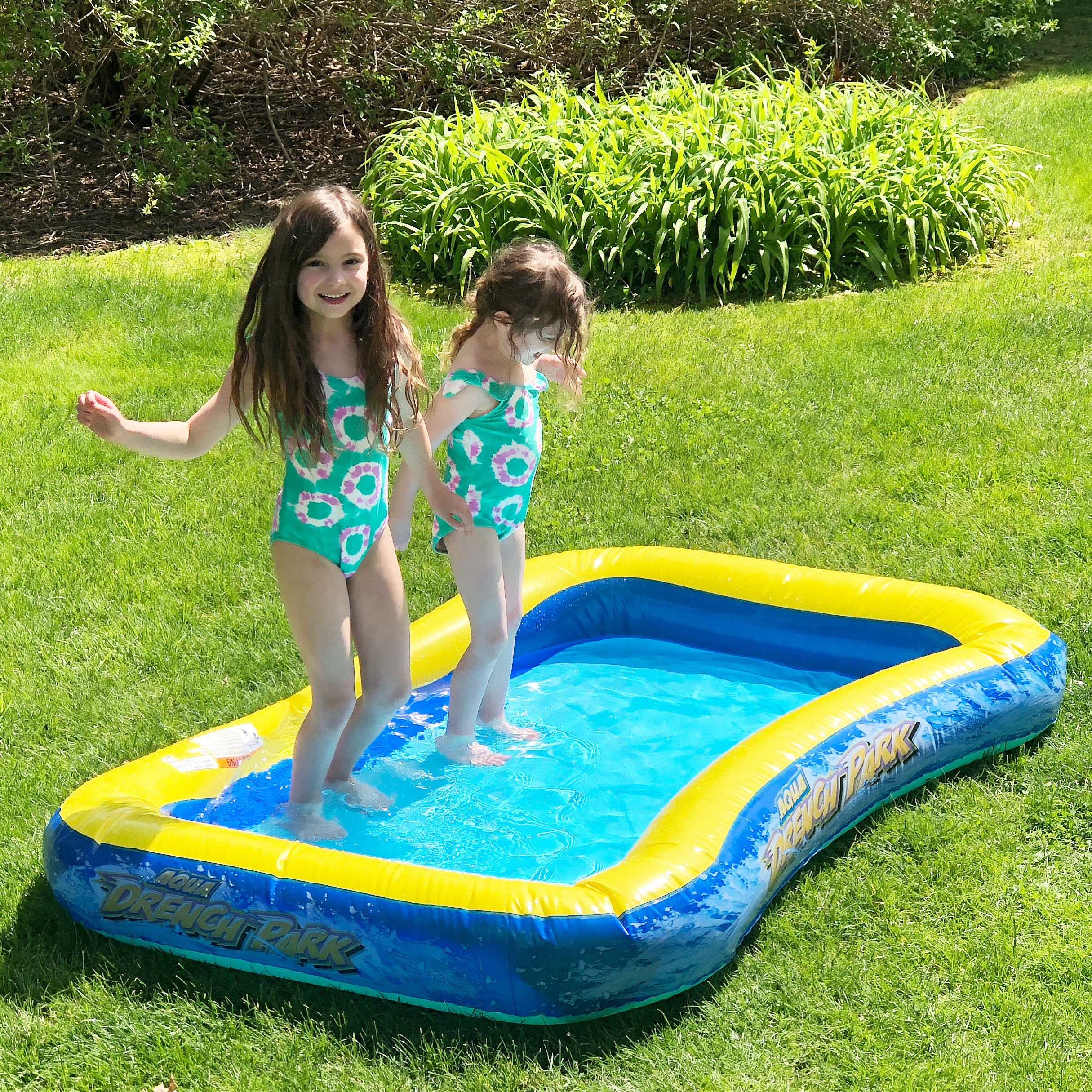 little girls playing in outdoor blow up pool for summer