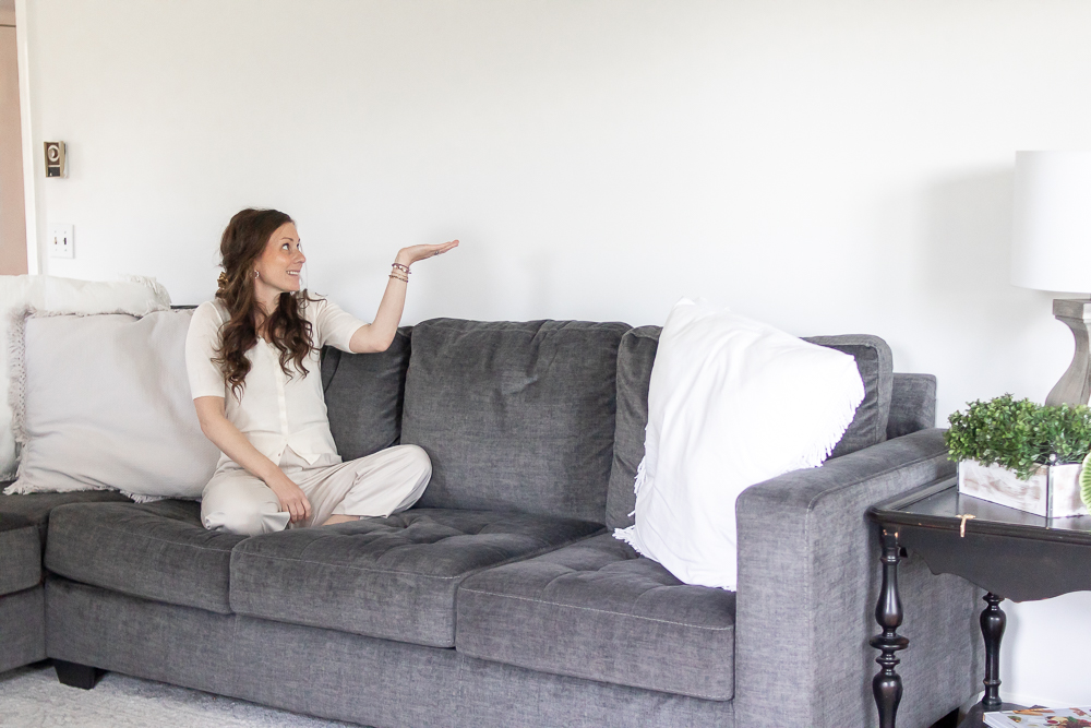 woman holding hand up at blank space above couch