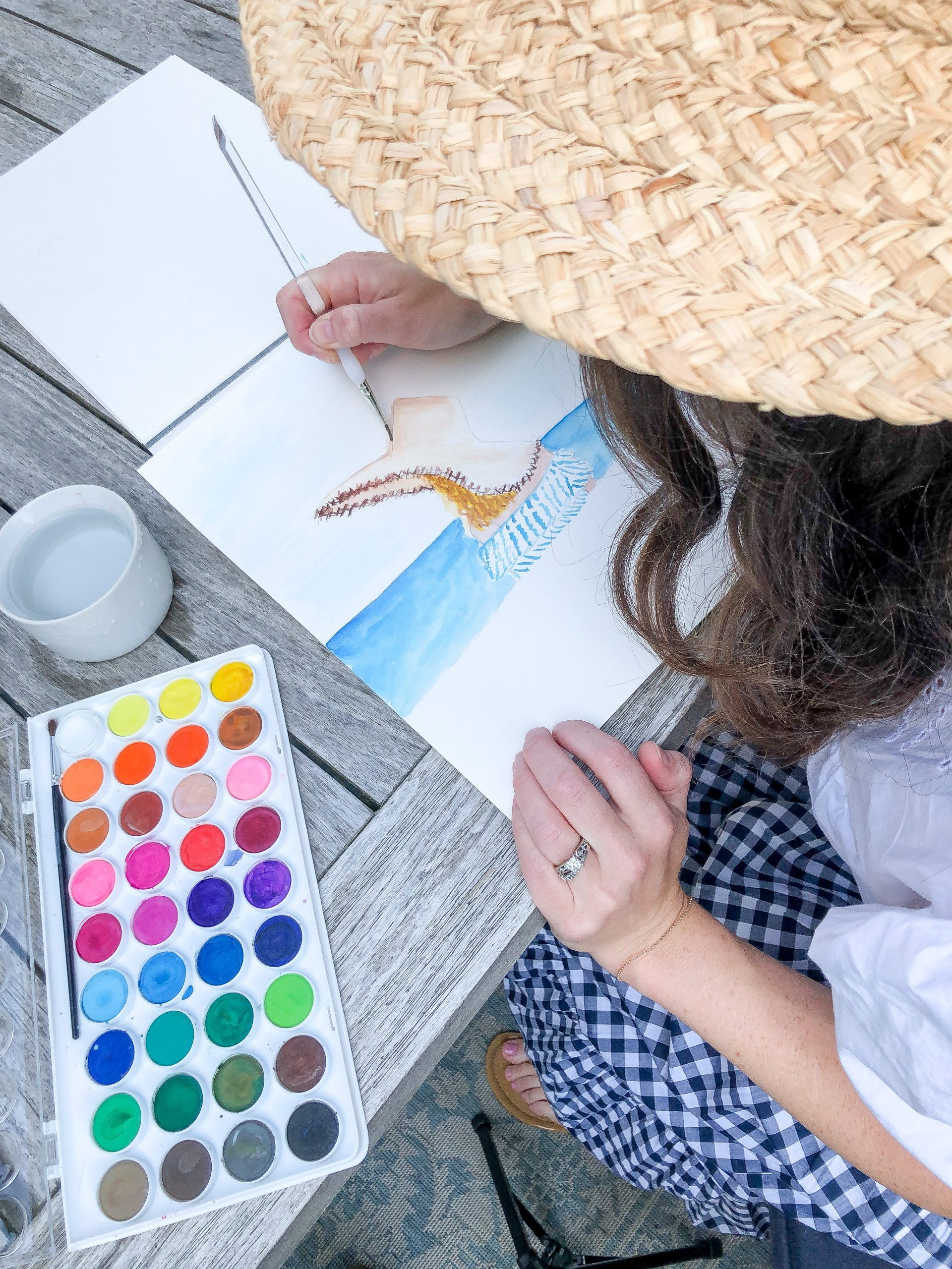 woman watercolor painting at a table