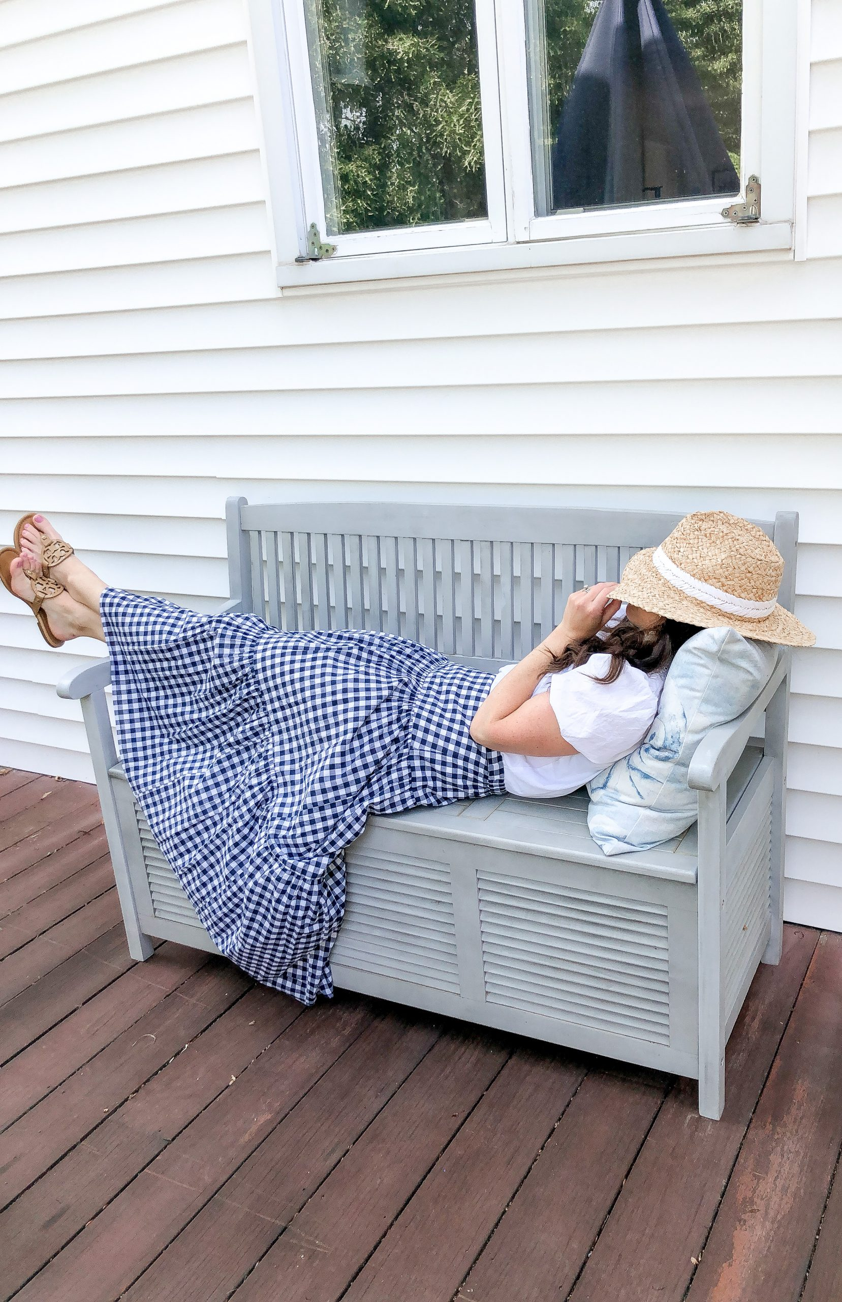 Woman in gingham skirt laying on blue bench with straw hat over her face