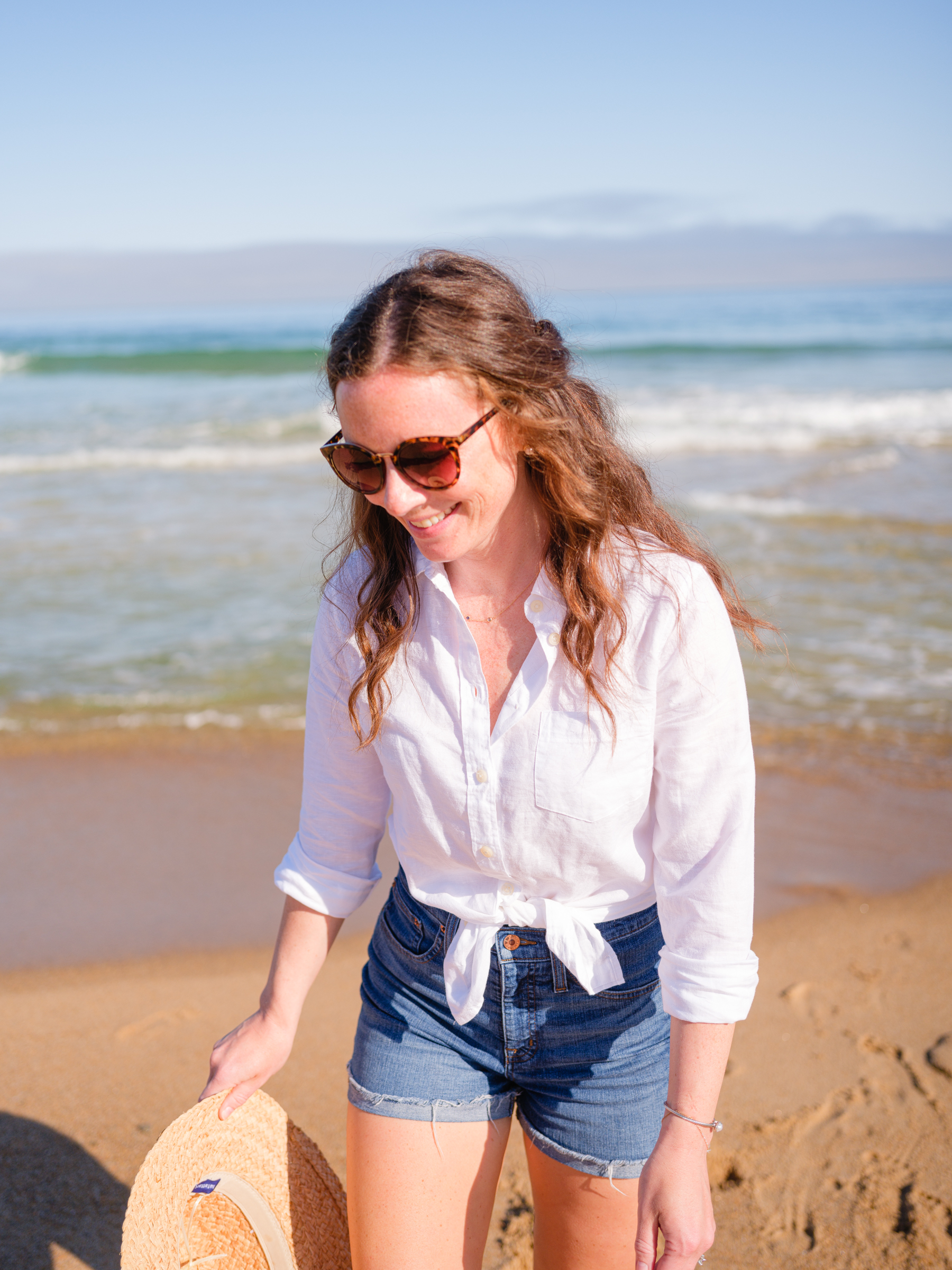 woman in white button up on beach