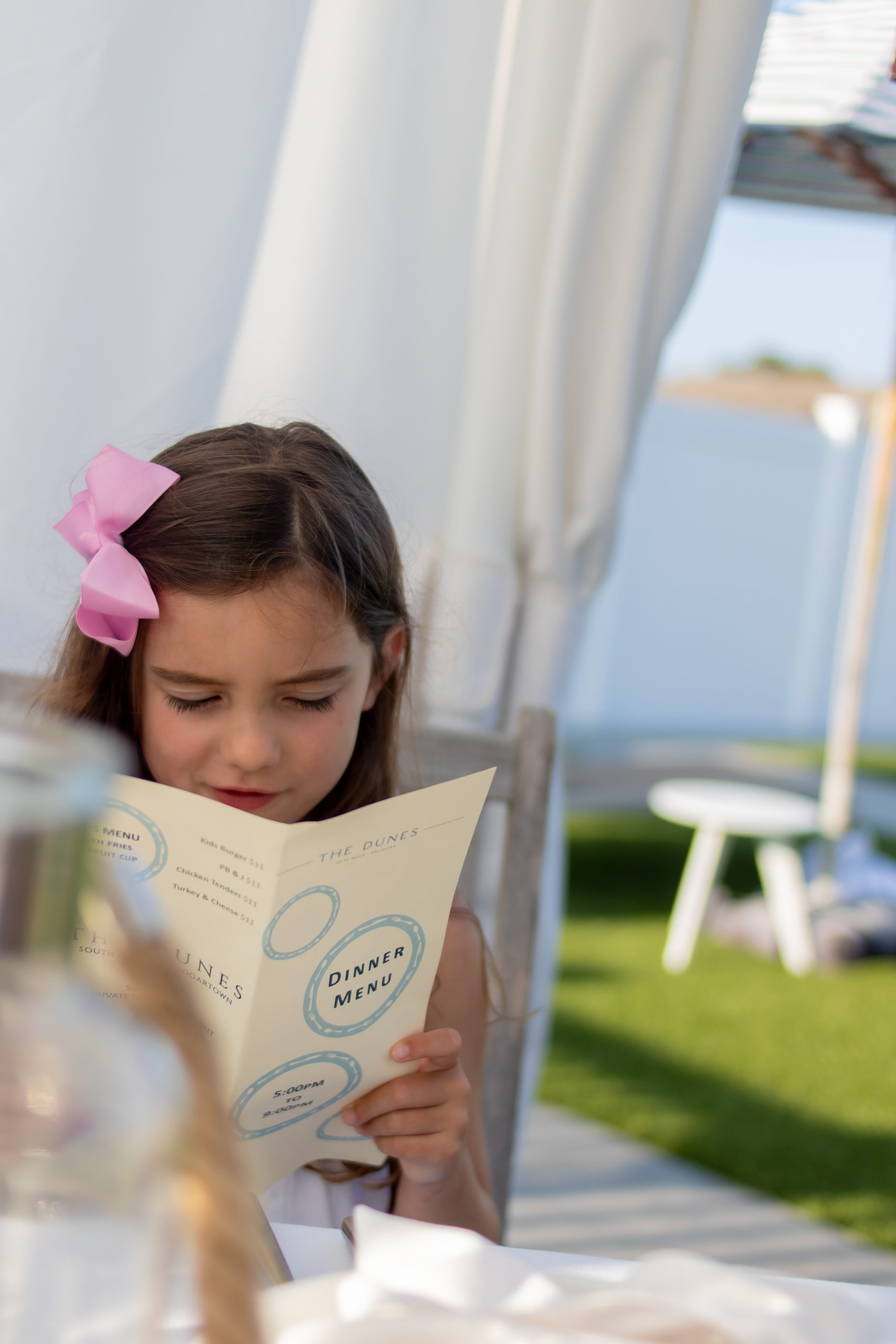 little girl reading Dunes menu at Winnetu