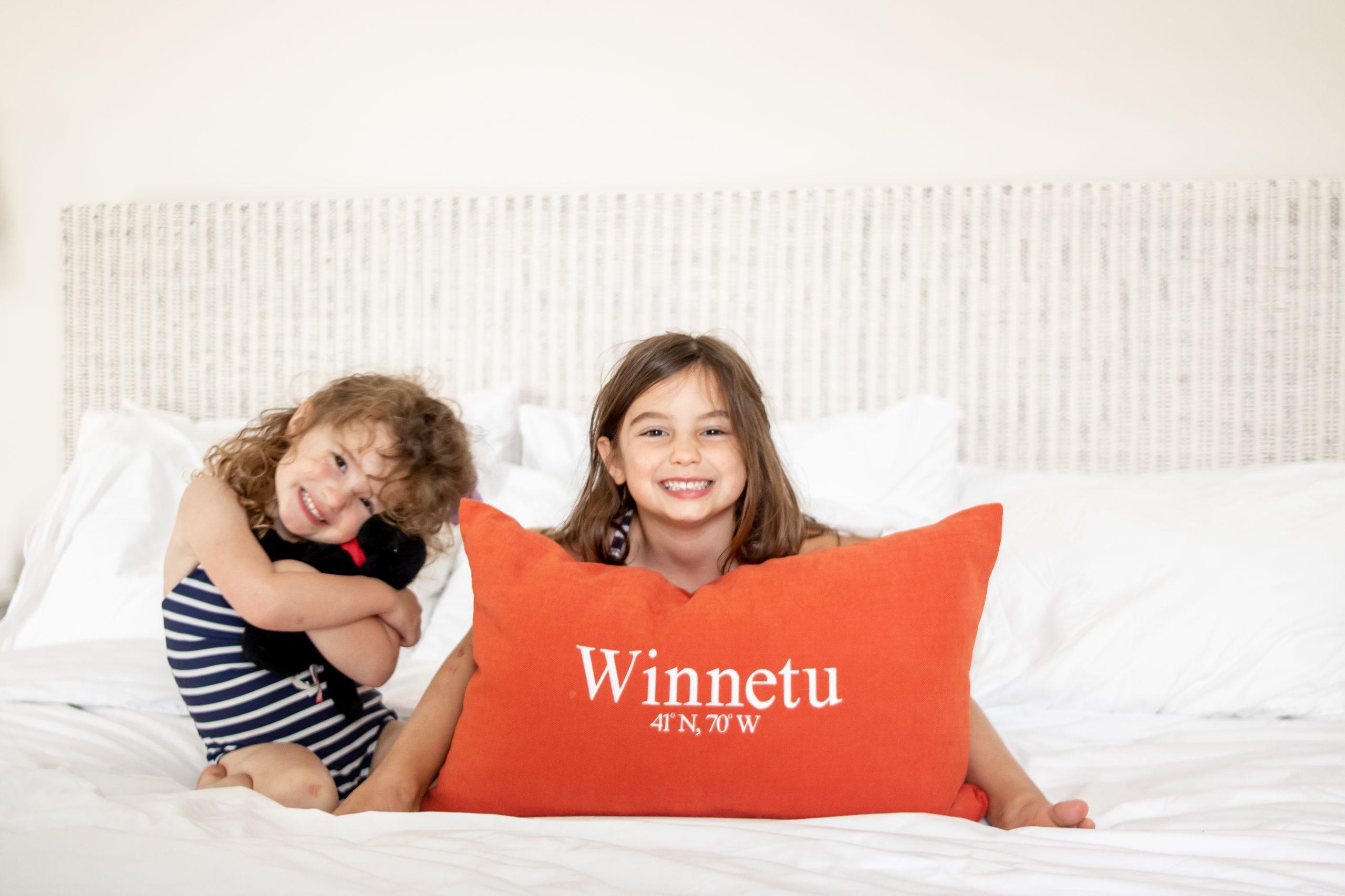 little kids sitting on bed at Winnetu Oceanside Resort