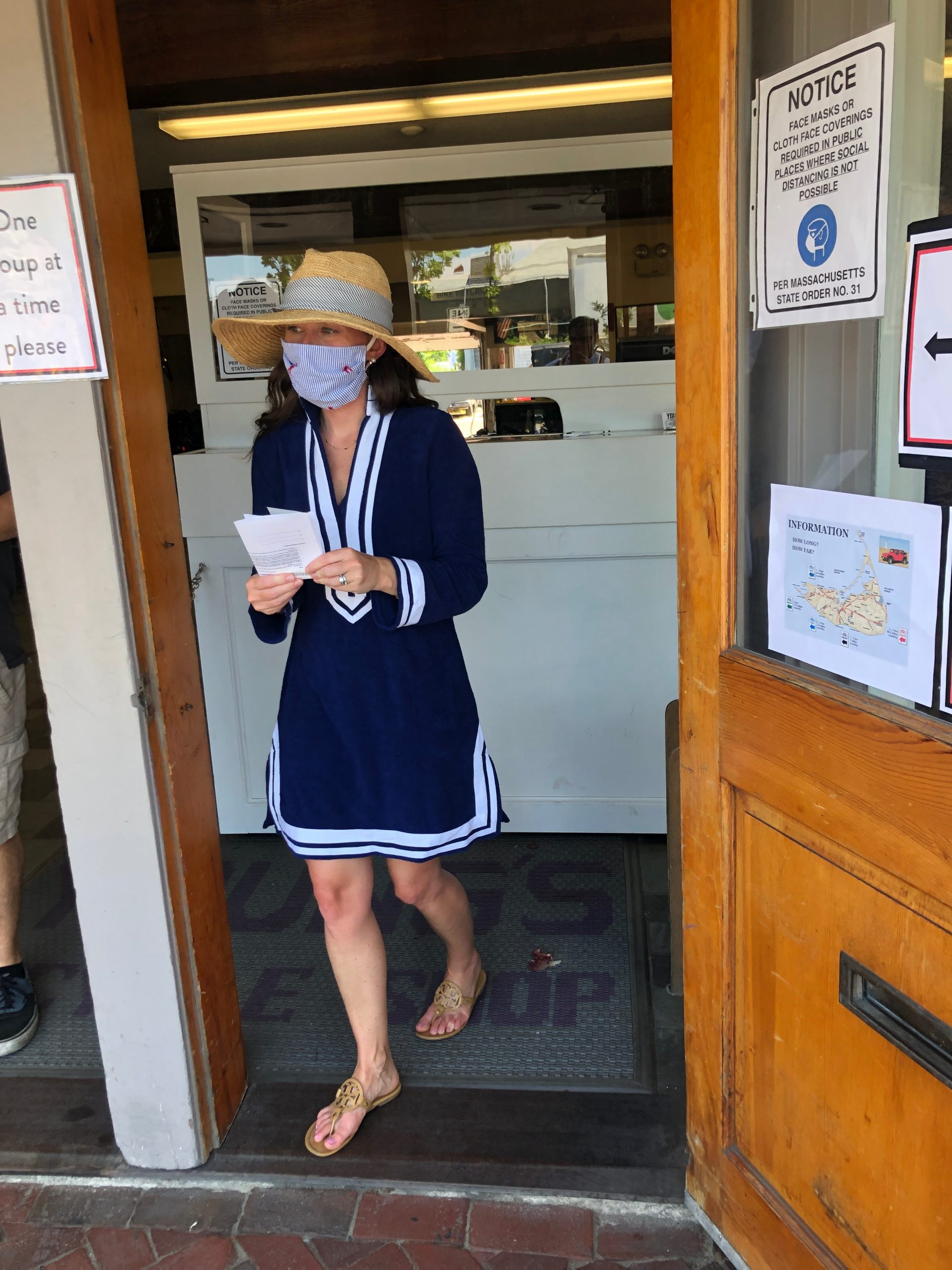 woman walking out of Young's Bicycle Shop in Nantucket wearing mask