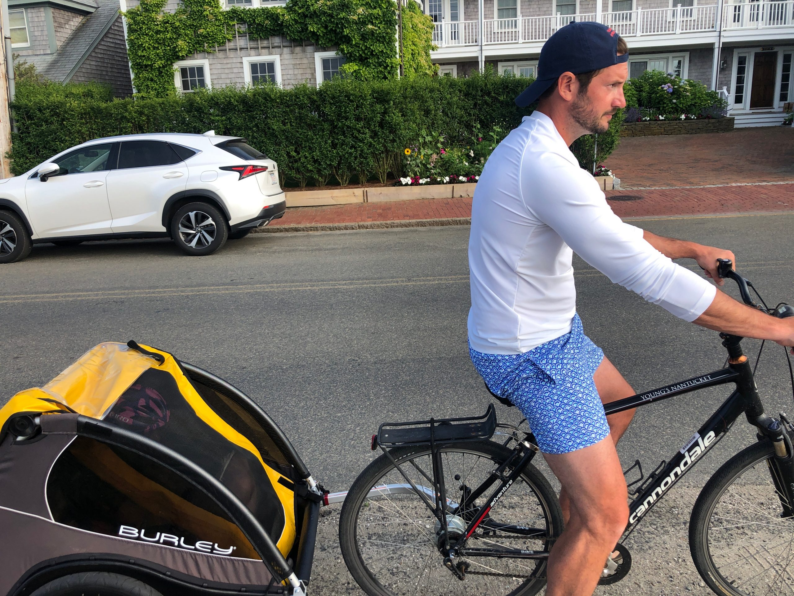 man riding bike with burley cub attached in nantucket