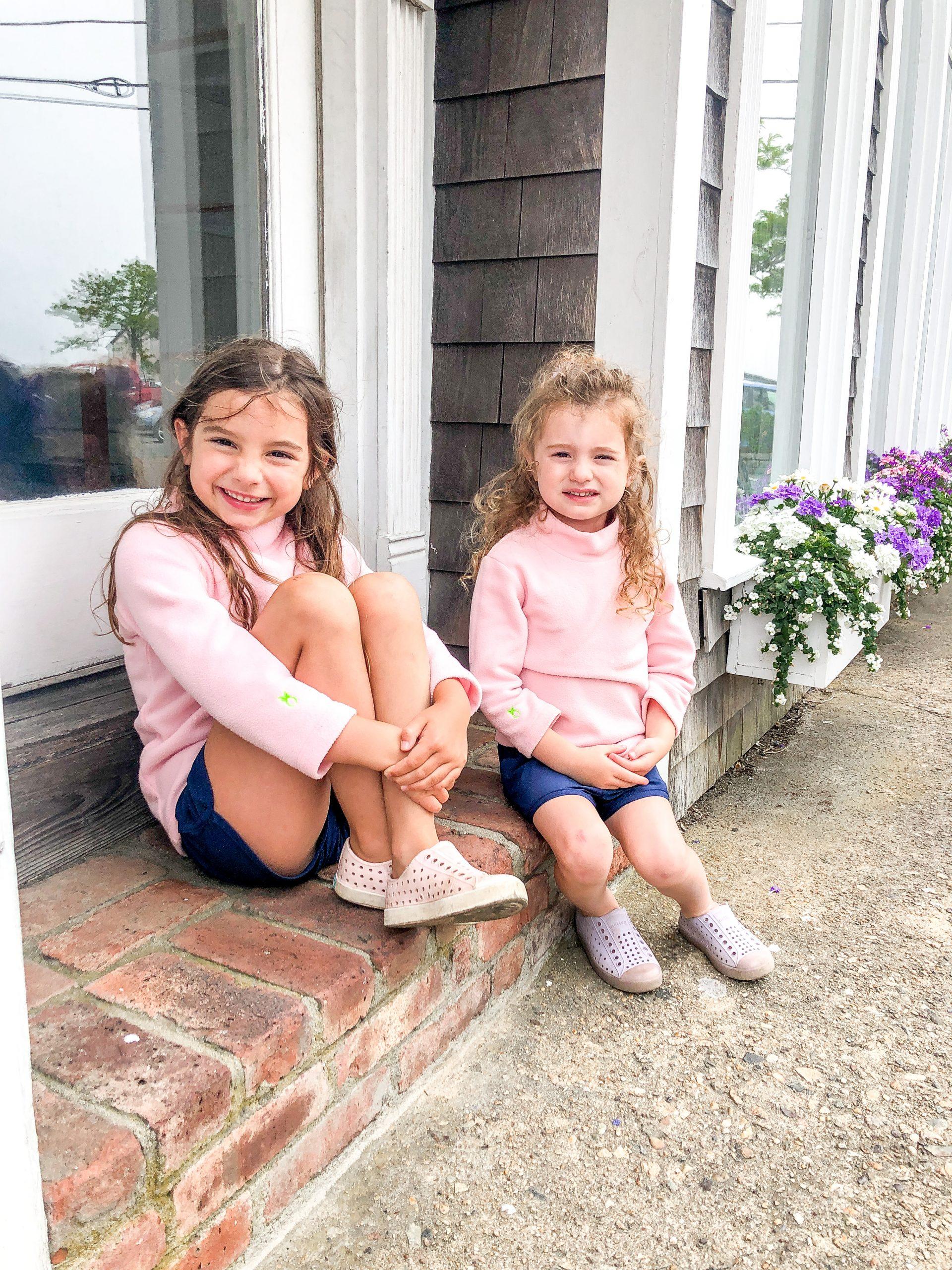 little girls sitting on stoop outside shops in Edgartown wearing Dudley Stephens