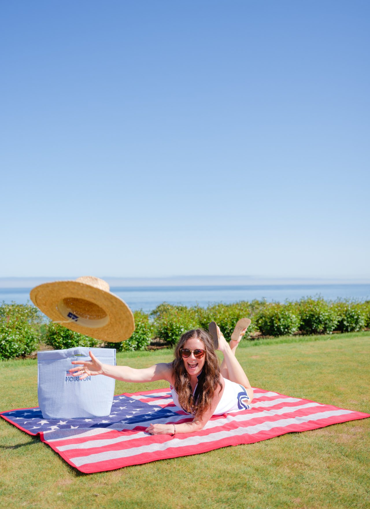 woman catching hat on american flag blanket