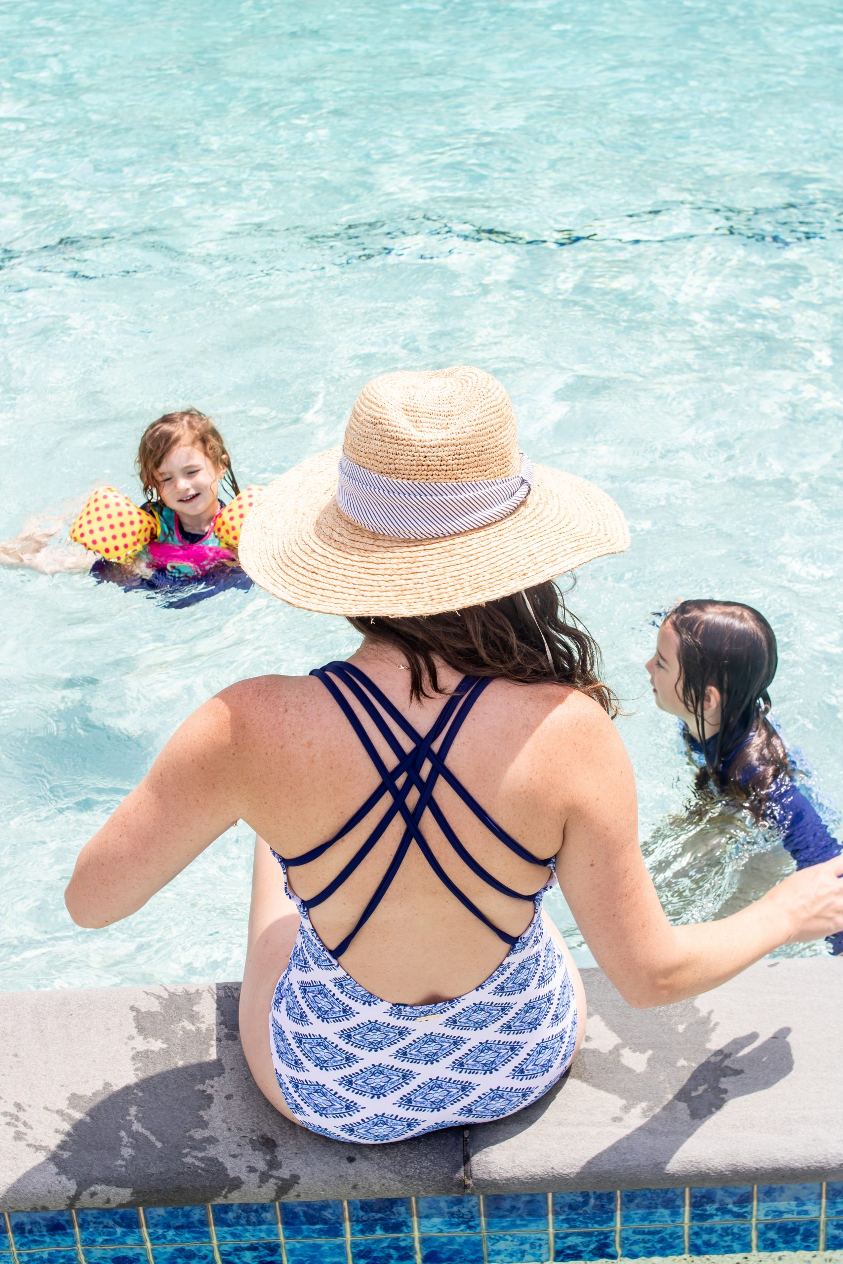 woman in bathing suit and beach hat sitting poolside watching children play at The Nantucket