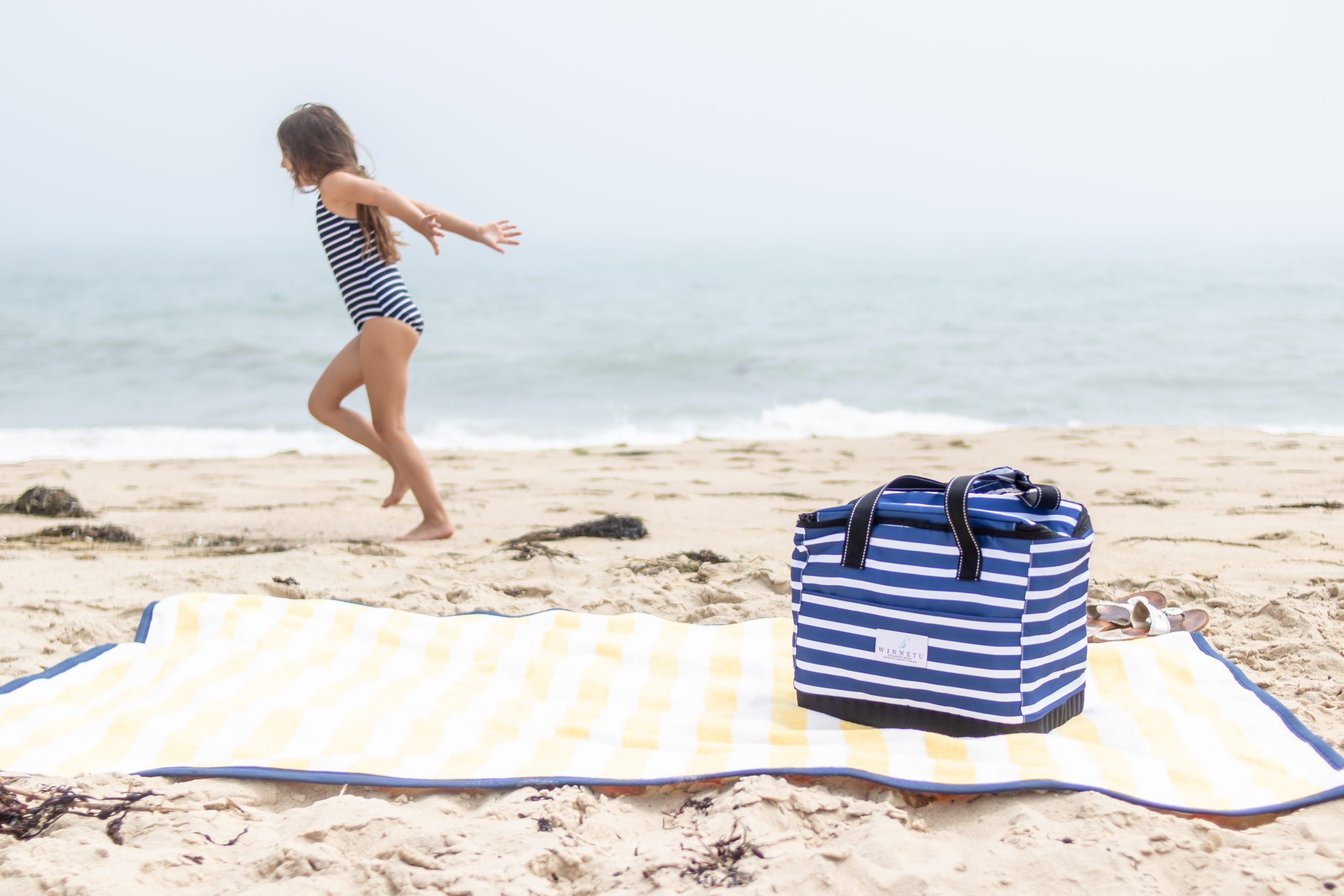 little girl running across beach in front of blanket with cooler winnetu