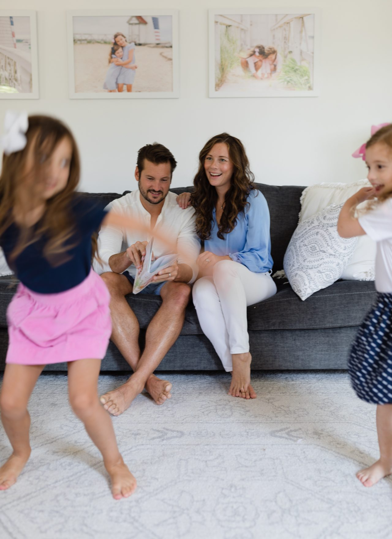 Mom and Dad on couch looking at photo book while girls dance in front of them