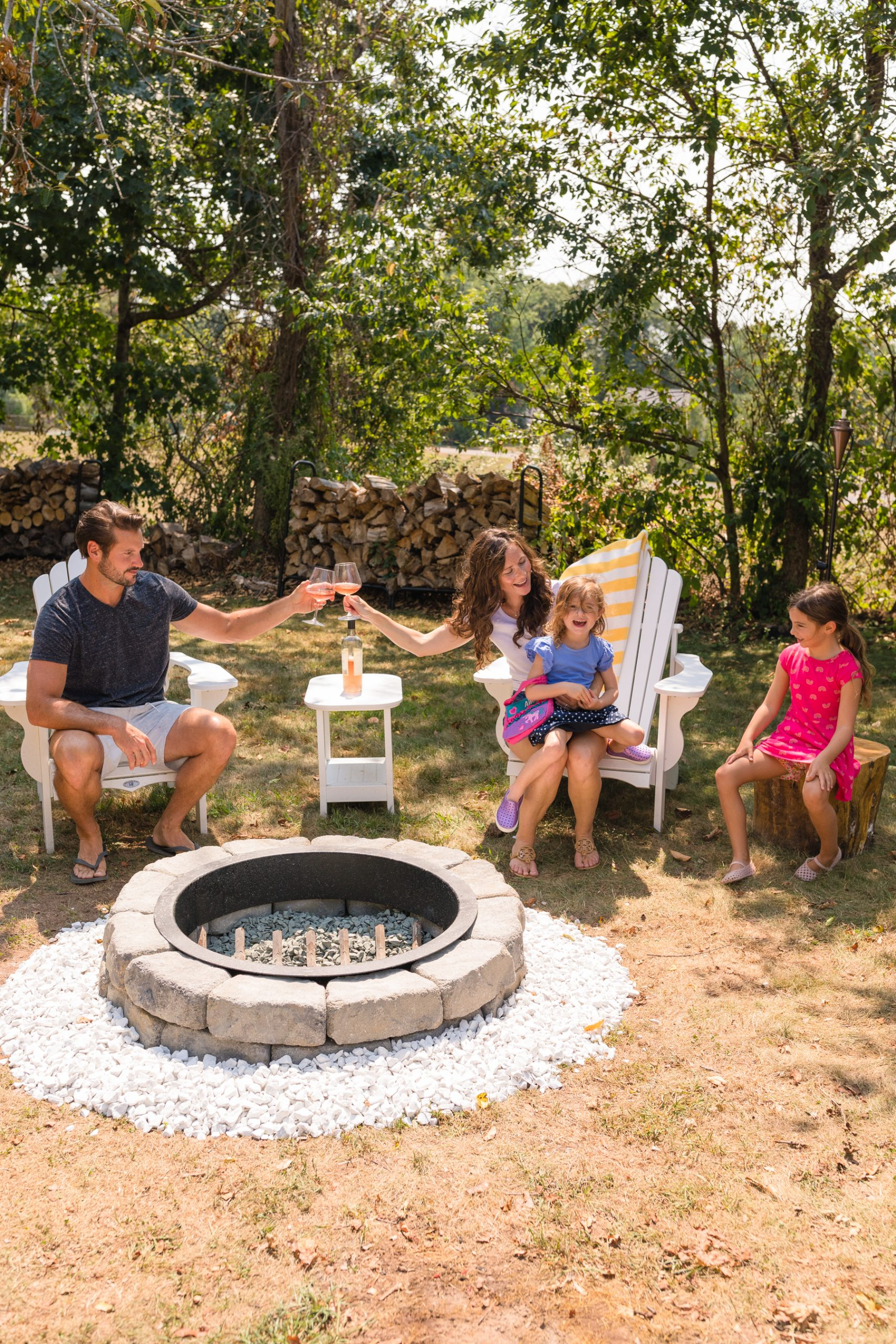 family sitting around diy fire pit cheering to life lately