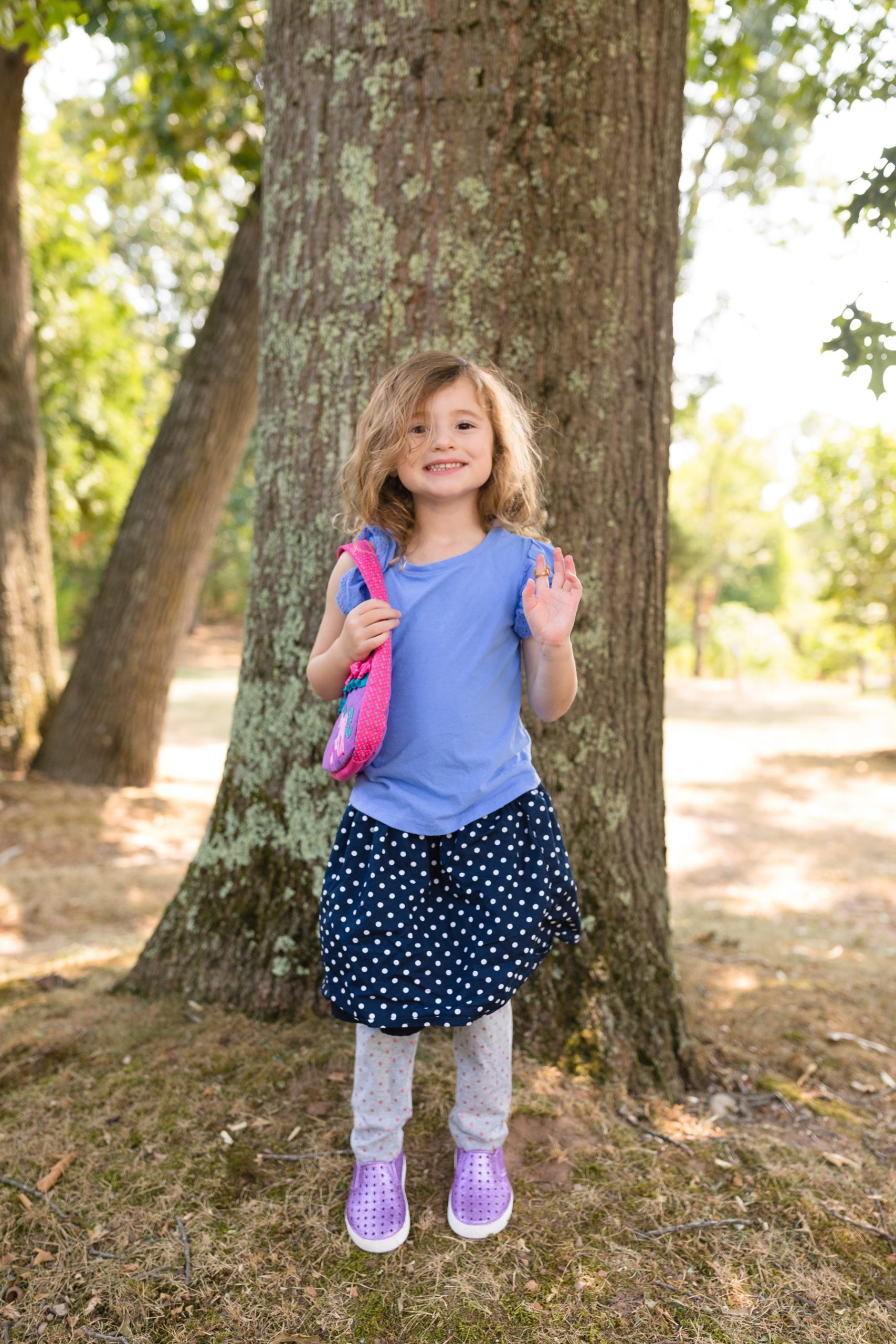 four year old in mismatched polka dot skirt, polka dot pants, purple shoes, purse