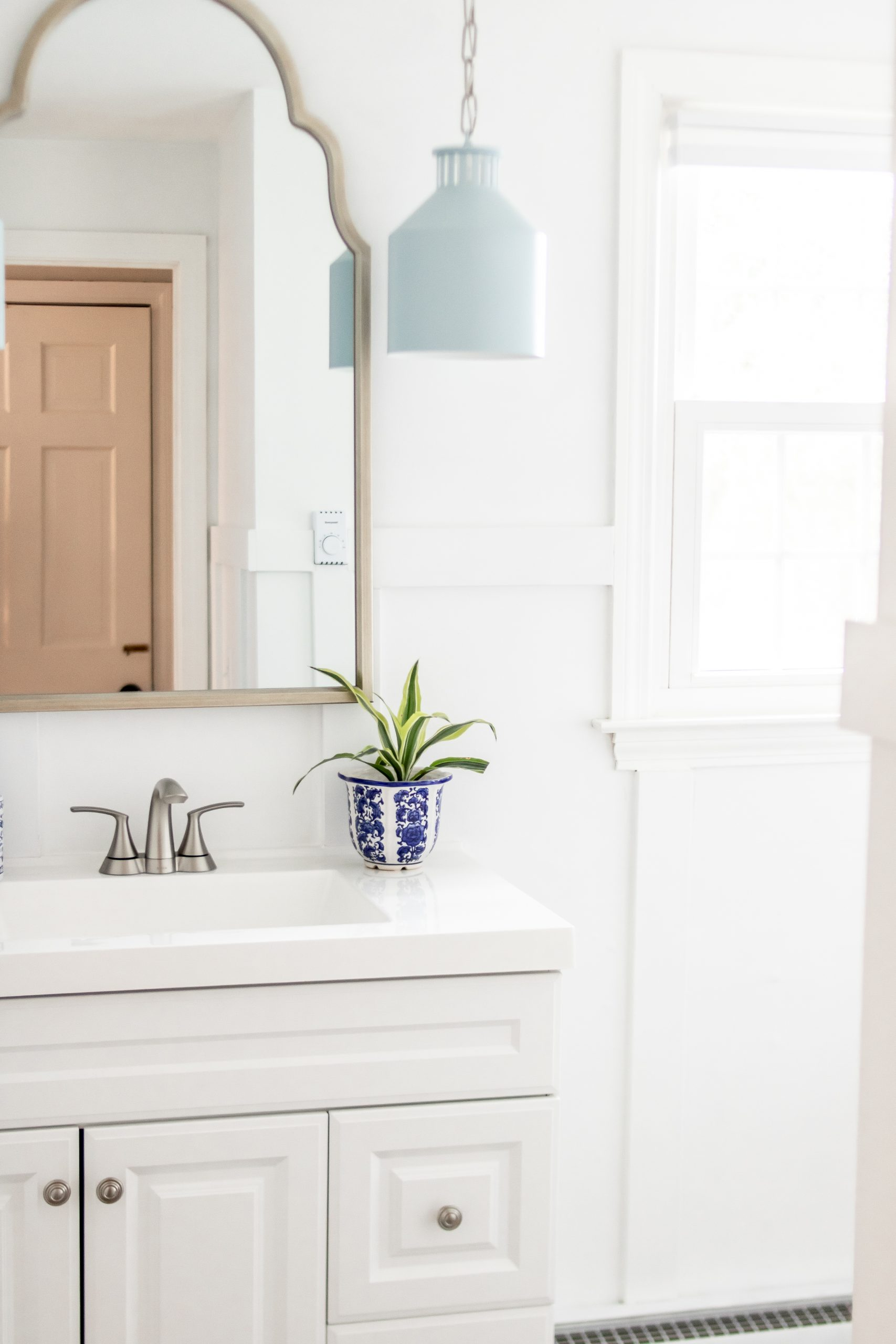 bright white bathroom with blue pendant light fixtures