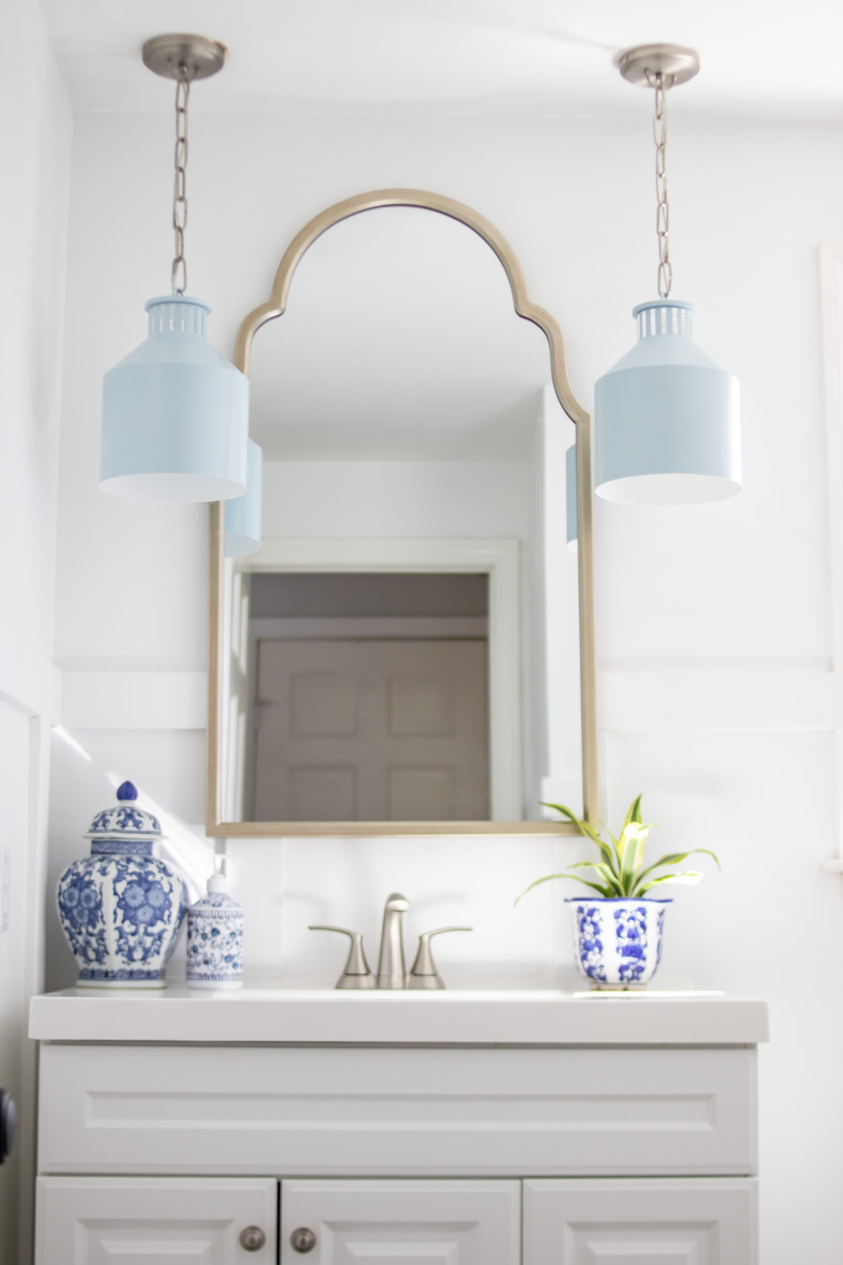 Cape Cod inspired bathroom light blue pendant lights arch mirror white vanity blue ginger jar decor
