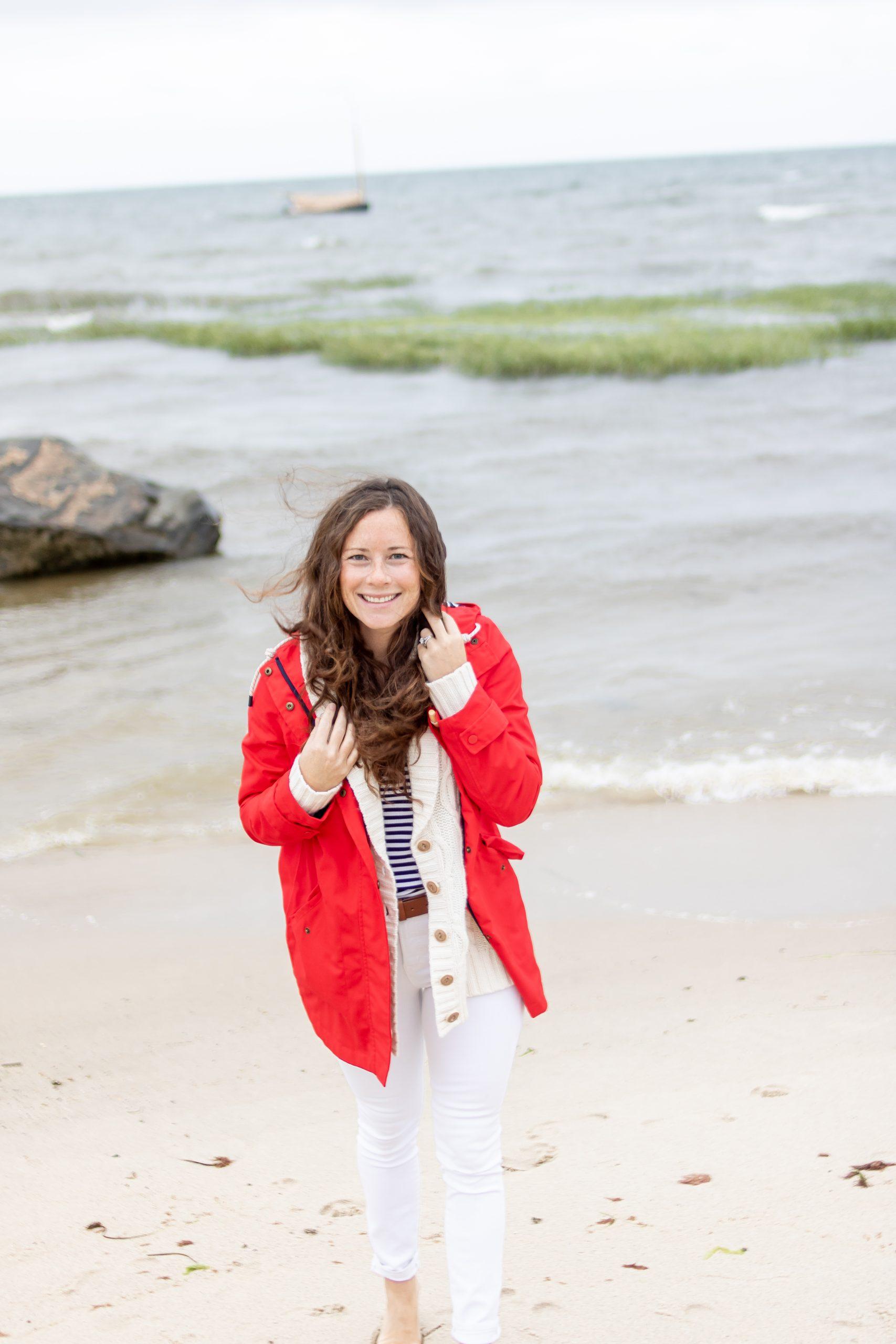 Woman in red rain coat walking on Breakwater Beach in Brewster in the Fall