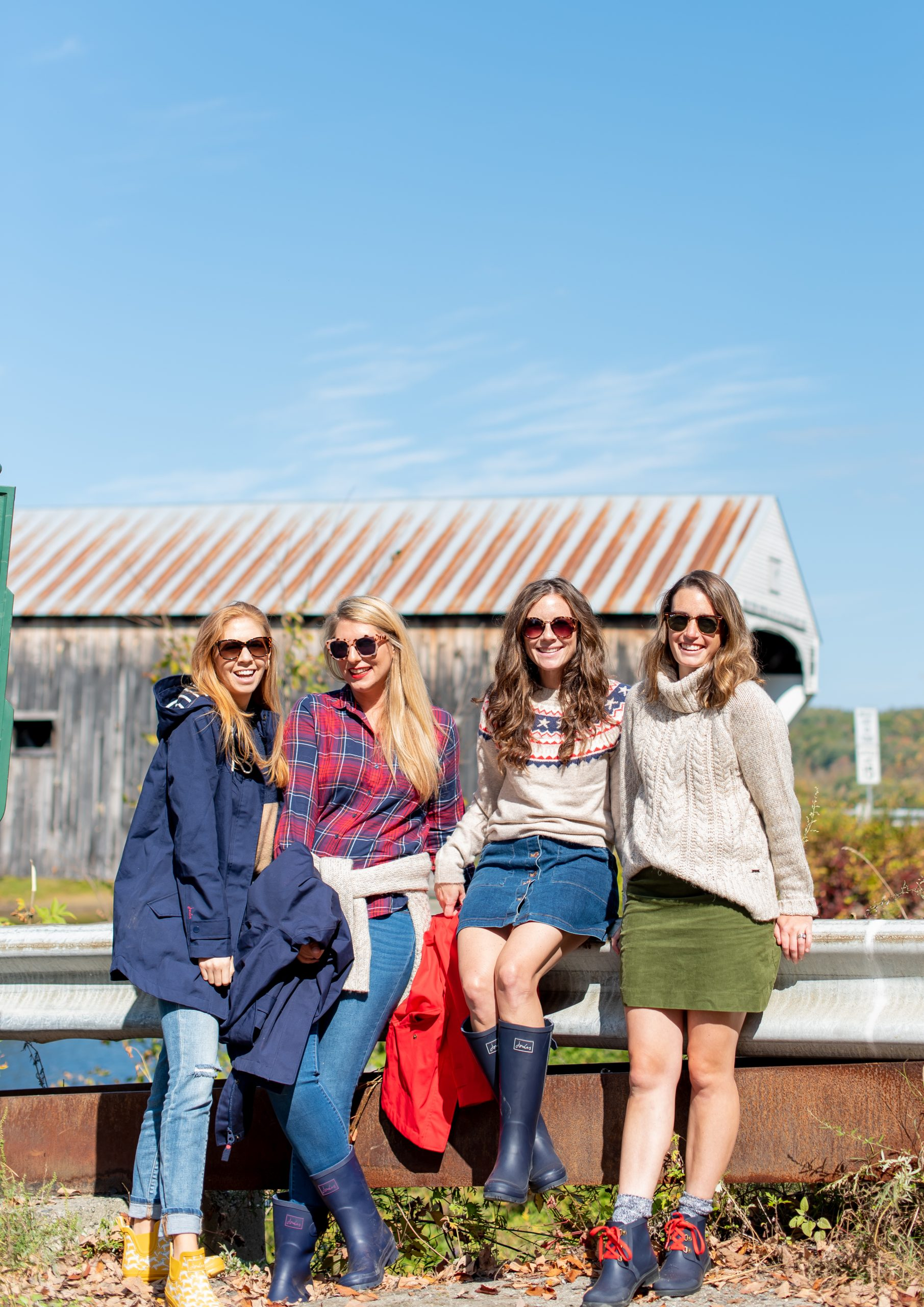 Girls sitting in front of Vermont Covered Bridge wearing Joules