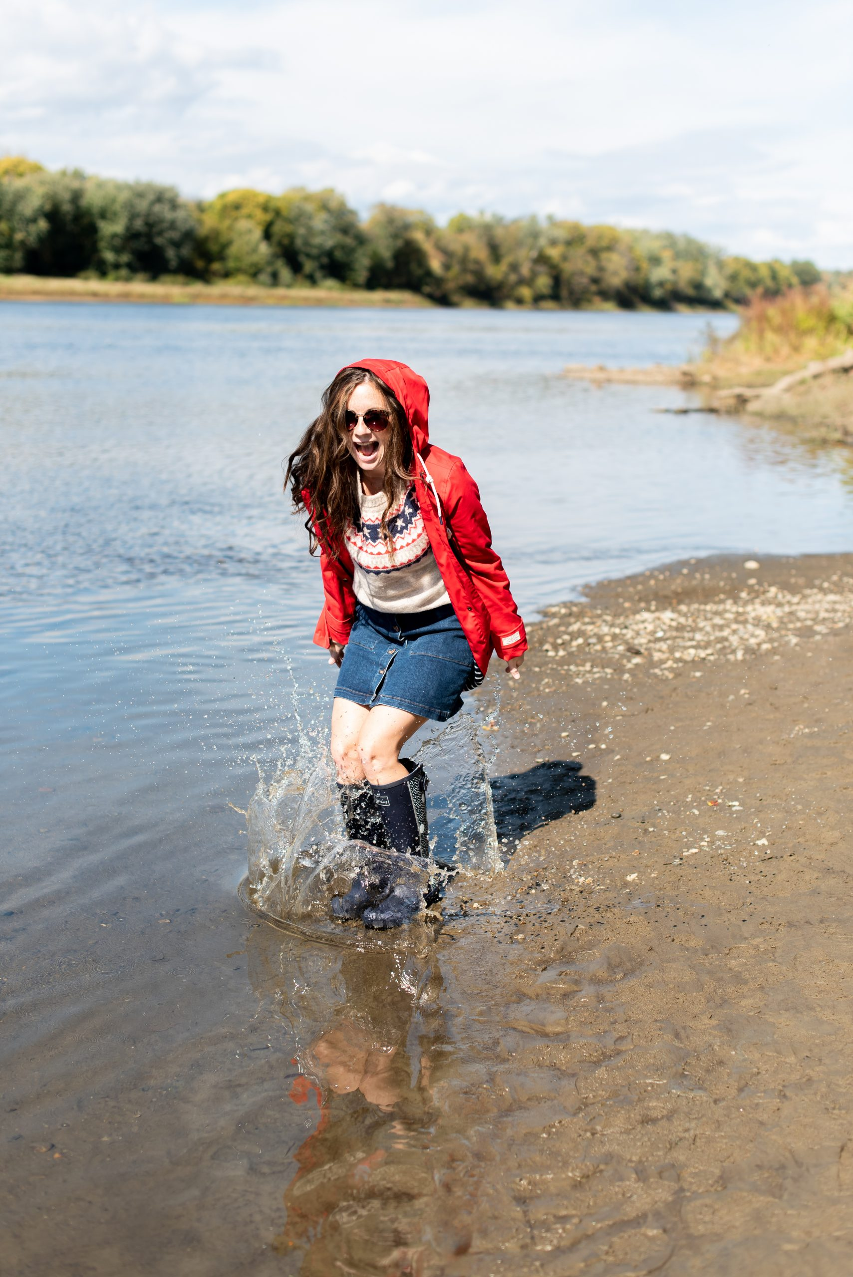 girl jumping into puddle wearing red raincoat and navy rain boots by Joules