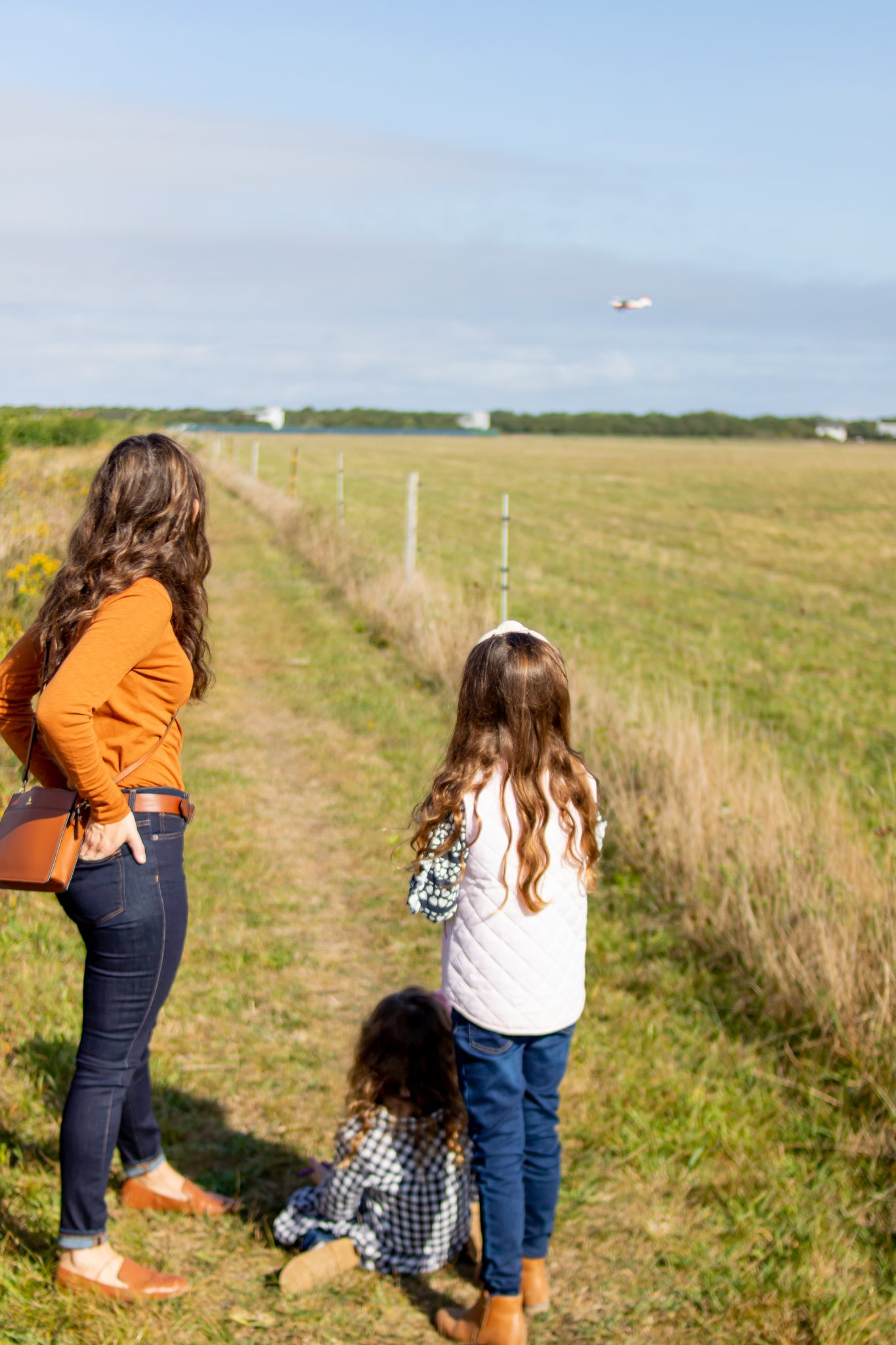 Mom and daughters looking at airplane taking off at Katama Airfield