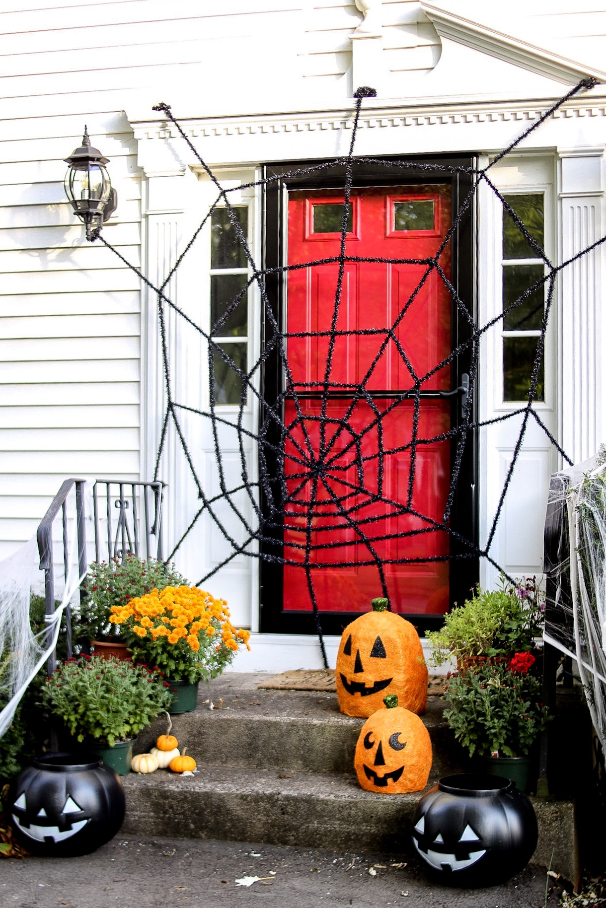 black spider web over red front door with mums and faux pumpkins