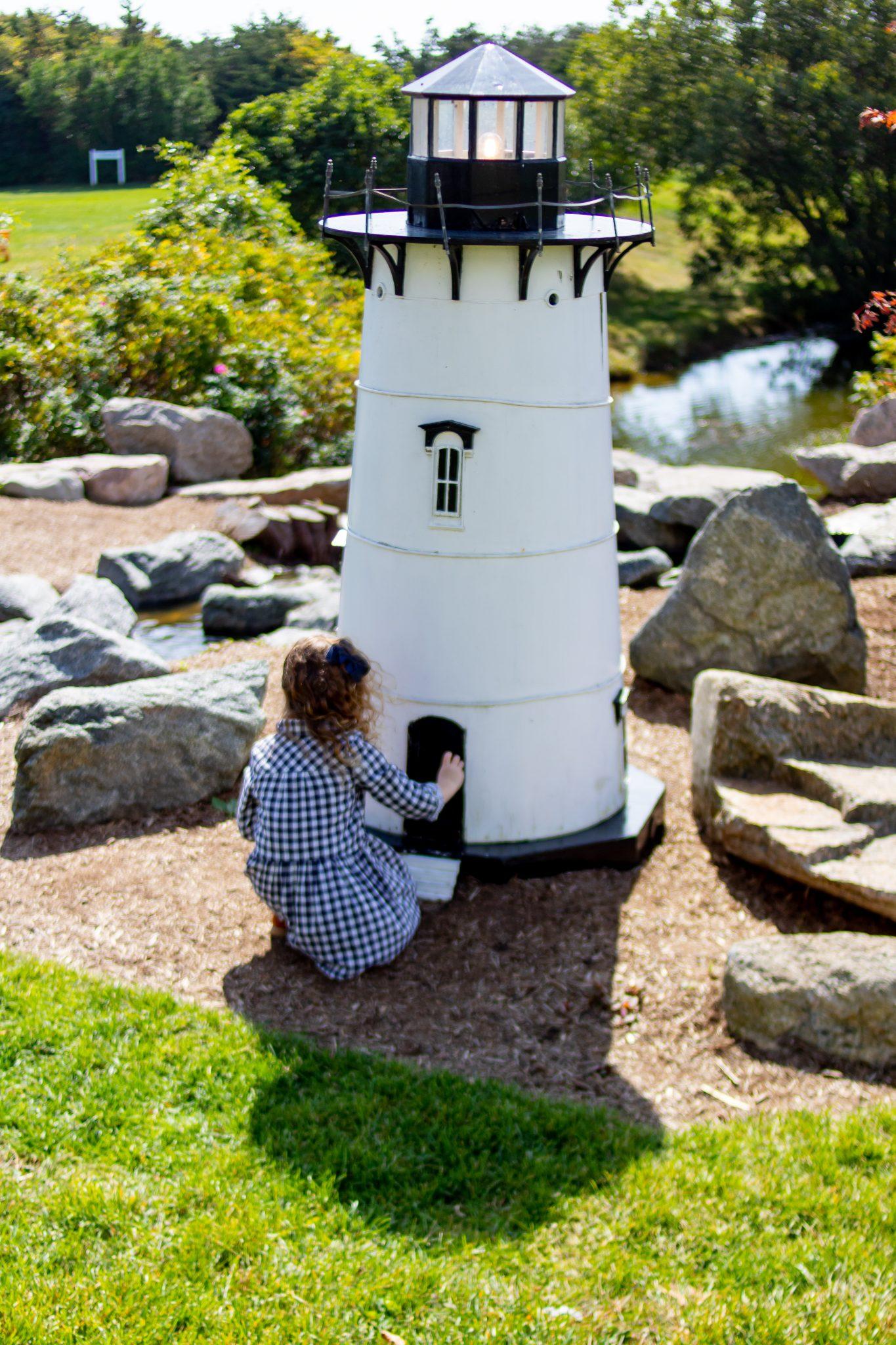 Little girl knocking on door of lighthouse at Winnetu
