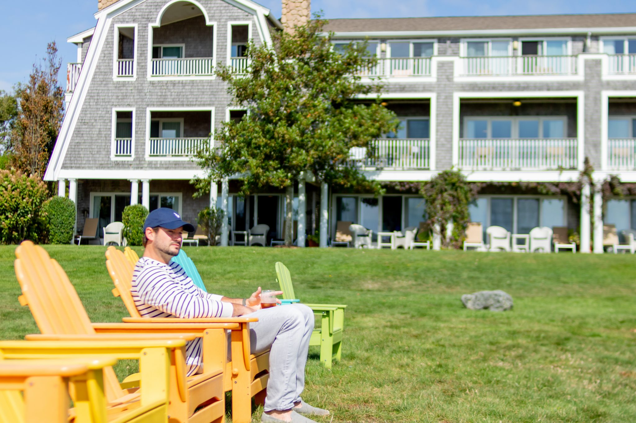 man sitting in colorful chairs on the Winnetu lawn