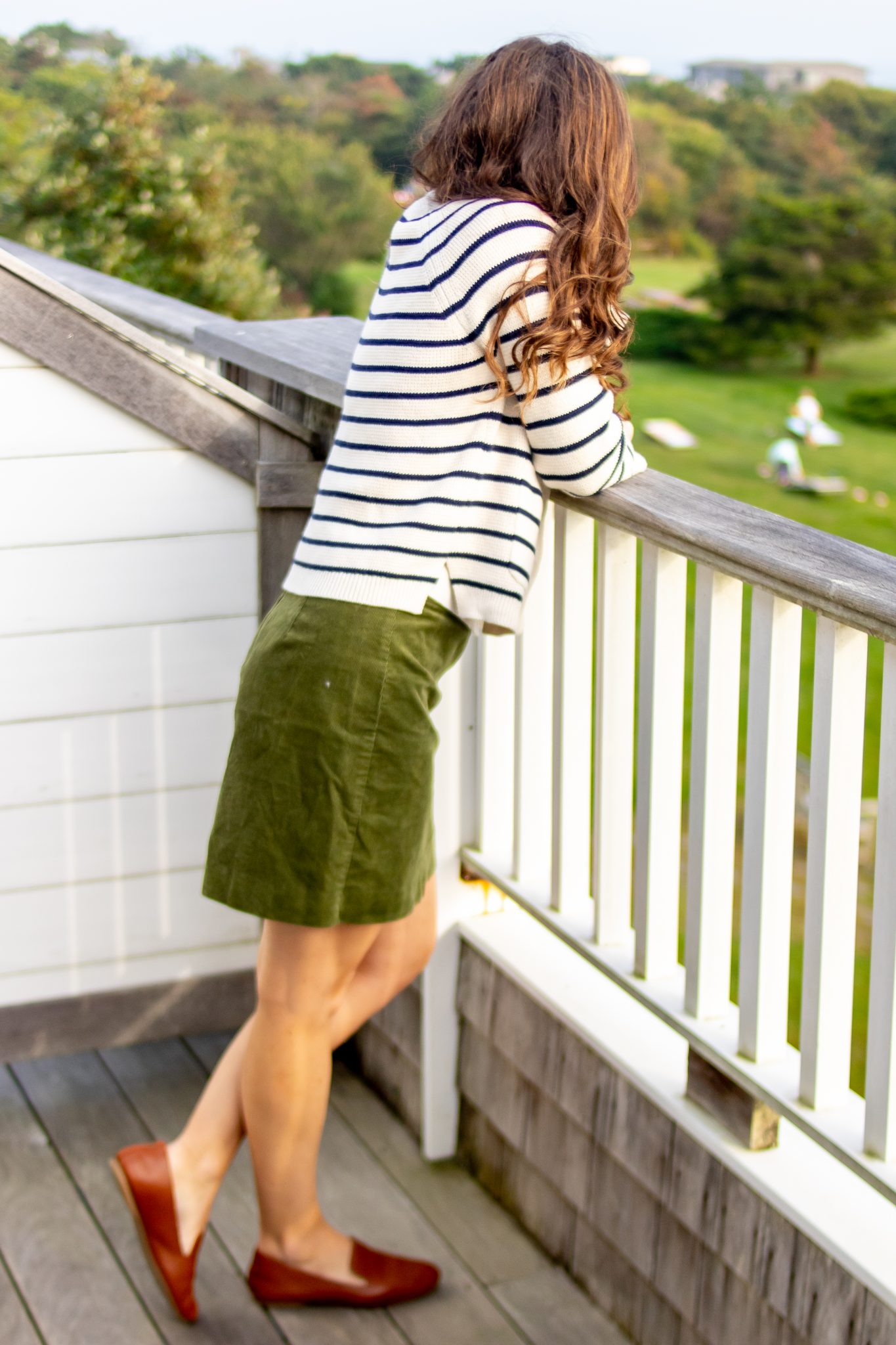 Woman in striped JCrew cardigan and green corduroy skirt standing on balcony at Winnetu