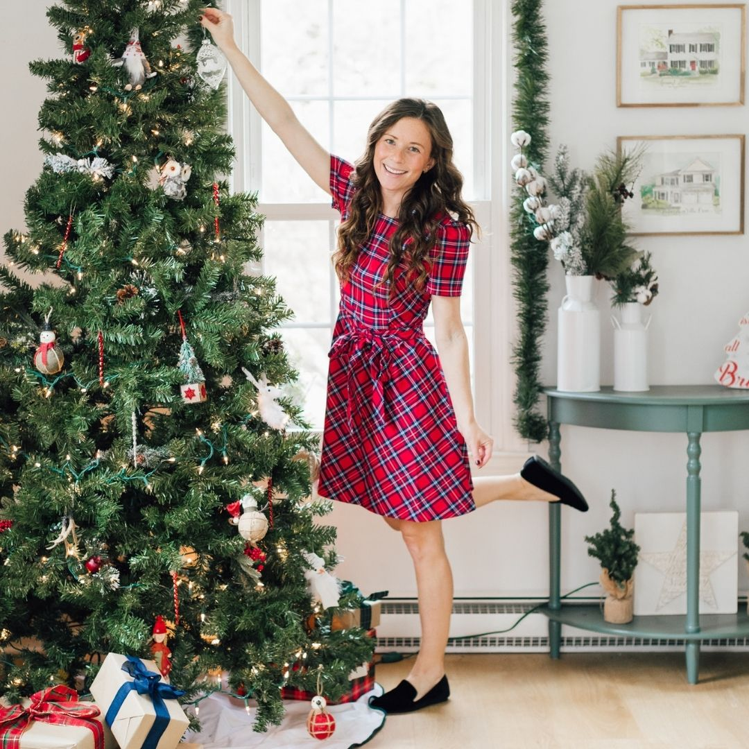 girl in plaid dress decorating christmas tree